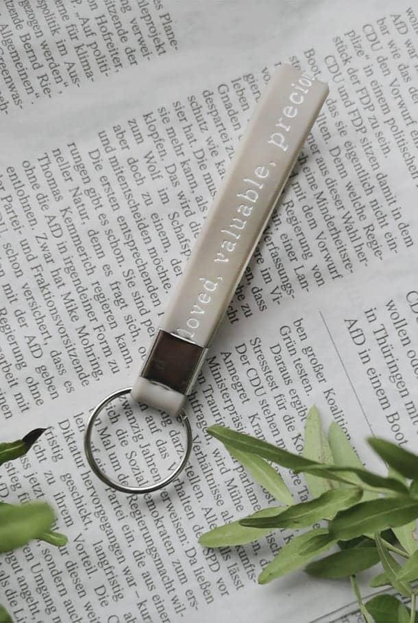 Nyckelringsband i gråbeige: Loved, valuable, precious